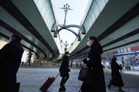 People wearing protective masks walk along an underpass on Feb. 8, 2021, in Tokyo. (AP Photo/Eugene Hoshiko)