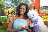 "This image released by Netflix shows former first lady Michelle Obama with Busy, a bee puppet, left, Mochi, a pink round puppet, and Waffles, a furry puppet with waffle ears on the set of the children's series ""Waffles + Mochi."" (Adam Rose/Netflix via AP)"