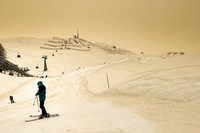 Skiers wearing protective face masks ski as Sahara sand colors the snow and the sky orange in the Alpine resort of Anzere, Switzerland, on Feb. 6, 2021. (Laurent Gillieron/Keystone via AP)