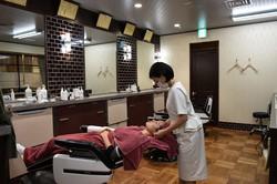 都内の美容室でマスク着用で働く女性(Bloomberg)