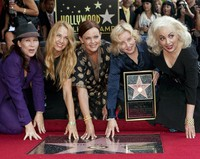 The female band The Go-Go's, from left, Kathy Valentine, Charlotte Caffey, Belinda Carlisle, Gina Schock and Jane Wiedlin, pose at their star on the Hollywood Walk of Fame in Los Angeles on Aug. 11, 2011. (AP Photo/Damian Dovarganes)