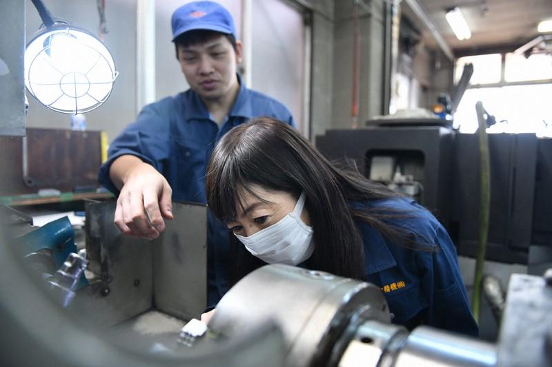 作業場で従業員と話し合うダイヤ精機の諏訪貴子さん(右)=東京都大田区で、宮間俊樹撮影