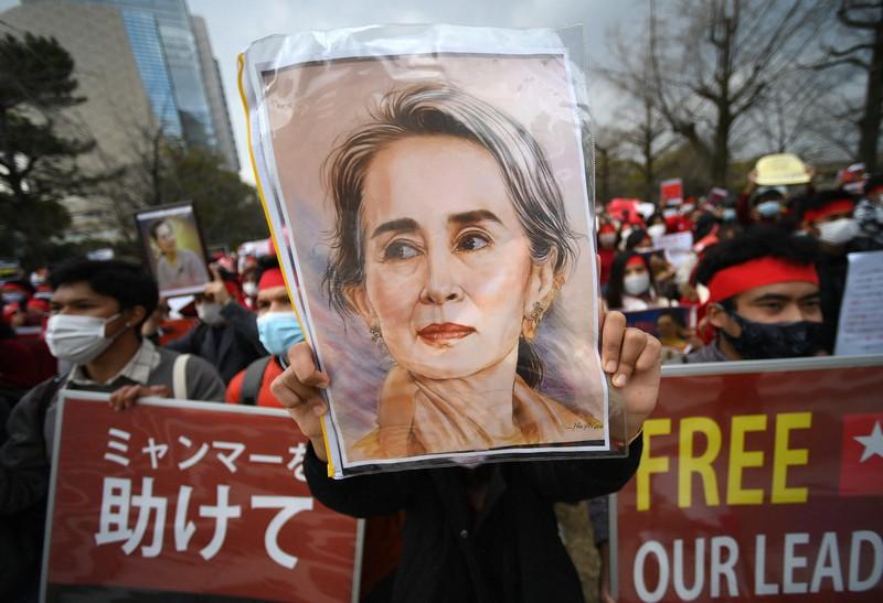 アウンサンスーチー氏の肖像画を掲げ、行進する人たち=大阪市中央区の大阪城公園で2021年2月7日午後2時、久保玲撮影