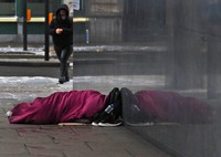 A rough sleeper seeks shelter close to a wall in London, on Feb. 8, 2021. (AP Photo/Frank Augstein)