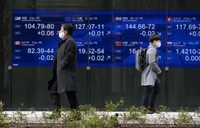 Men walk past screens showing foreign exchange rates at a securities firm in Tokyo on Feb. 12, 2021. (AP Photo/Hiro Komae)