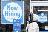"""In this Feb. 6, 2021 photo, a woman walks past a """"Now Hiring"""" sign displayed at a CD One Price Cleaners in Schaumburg, Illinois. (AP Photo/Nam Y. Huh)"""