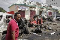 A man walks past wreckage at the scene of a bombing in Mogadishu, Somalia, on Feb. 13, 2021. (AP Photo/Farah Abdi Warsameh)
