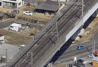 Power poles supporting overhead wires on the Tohoku Shinkansen lines are seen leaning on Feb. 14, 2021, a day after a quake, in Koriyama, Fukushima Prefecture, in this photo taken from a Mainichi helicopter.