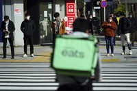 People wearing protective masks to help curb the spread of the coronavirus wait for a traffic light at an intersection, on Feb. 8, 2021, in Tokyo. (AP Photo/Eugene Hoshiko)