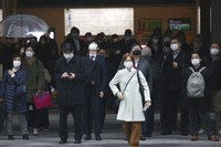 People wearing face masks to protect against the spread of the coronavirus wait for signals to turn green at a crossing in Tokyo, on Feb. 15, 2021. (AP Photo/Koji Sasahara)
