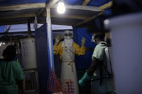 In this Nov. 20, 2014 file photo, an MSF Ebola heath worker is sprayed as he leaves the contaminated zone at the Ebola treatment center in Gueckedou, Guinea. (AP Photo/Jerome Delay-File)
