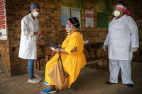 Putseltso Lesofe, right, and Carol Ditshego, left, brief a patient before giving her a COVID-19 test at the Ndlovu clinic in Elandsdoorn, 200 km northeast of Johannesburg on Feb. 11, 2021. (AP Photo/Jerome Delay)
