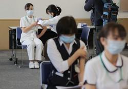新型コロナウイルスのワクチン接種を受ける医療従事者(左奥)。手前は経過観察のため待機する人=東京都目黒区の国立病院機構東京医療センターで2021年2月17日午前9時17分(代表撮影)