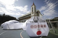 A person stands inside a portable epidemiological insulation unit during a media presentation, in Bogota, Colombia, on Feb. 16, 2021.  (AP Photo/Fernando Vergara)