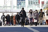 People wearing face masks to protect against the spread of the coronavirus walk down a street in Tokyo, on Feb. 17, 2021. (AP Photo/Koji Sasahara)