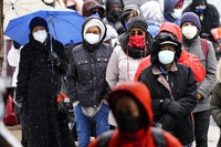 In this Feb. 19, 2021, file photo, people wait in line at a 24-hour, walk-up COVID-19 vaccination clinic hosted by the Black Doctors COVID-19 Consortium at Temple University's Liacouras Center in Philadelphia. (AP Photo/Matt Rourke, File)