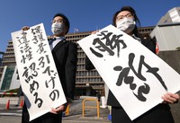 """Lawyers representing the plaintiffs hold up banners including one reading """"Suit won,"""" following the ruling by the Osaka District Court in the city of Osaka's Kita Ward on Feb. 22, 2021. (Mainichi/Rei Kubo)"""