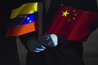 In this March 30, 2020 file photo, Venezuela's Foreign Minister Jorge Arreaza, wearing protective gloves as a preventive measure against the spread of the new coronavirus, holds a Venezuelan and Chinese flag as medical specialists and supplies arrive from China at the Simon Bolivar International Airport in La Guaira, Venezuela. (AP Photo/Matias Delacroix)