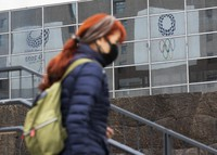 A woman walks past logos of the postponed Tokyo 2020 Olympic and Paralympic Games in Tokyo on Feb. 18, 2021. (AP Photo/Hiro Komae)