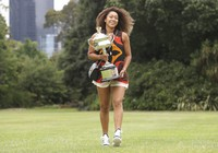 Japan's Naomi Osaka carries the Daphne Akhurst Memorial Cup during a photo shoot at Government House the day after defeating the United States' Jennifer Brady in the women's singles final at the Australian Open tennis championship in Melbourne, Australia, on Feb. 21, 2021. (AP Photo/Hamish Blair)