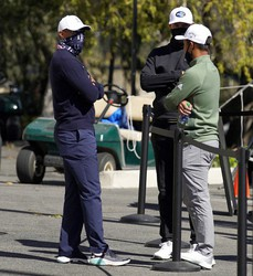 From left, Tiger Woods, Dustin Johnson and Xander Schauffele talk after high winds suspended play during the third round of the Genesis Invitational golf tournament at Riviera Country Club, on Feb. 20, 2021, in the Pacific Palisades area of Los Angeles. (AP Photo/Ryan Kang)