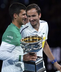 Serbia's Novak Djokovic, left, holds the Norman Brookes Challenge Cup as he talks with runner-up Russia's Daniil Medvedev after winning the men's singles final at the Australian Open tennis championship in Melbourne, Australia, on Feb. 21, 2021.(AP Photo/Mark Dadswell)