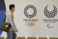 A man walks near an official shop of the Tokyo 2020 Olympic and Paralympic Games in Tokyo, Tuesday, Feb. 23, 2021. Japan began to roll out coronavirus vaccines on Wednesday, a critical move that might boost the Olympics. (AP Photo/Koji Sasahara)