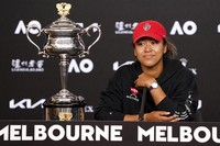 Japan's Naomi Osaka sits next to her trophy, the Daphne Akhurst Memorial Cup, at a press conference after defeating United States Jennifer Brady in the women's singles final at the Australian Open tennis championship in Melbourne, Australia, on Feb. 20, 2021. (Michael Dodge/Tennis Australia via AP)