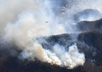 This photo taken from a Mainichi Shimbun helicopter shows the fourth day of wildfires in a mountain forest in Ashikaga, Tochigi Prefecture, on Feb. 24, 2021. A Self-Defense Force helicopter resumed firefighting efforts on the same morning. (Mainichi/Daiki Takikawa)