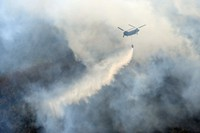 This photo taken from a Mainichi Shimbun helicopter shows a Self-Defense Force helicopter fighting the fourth day of wildfires that have burned in a mountain forest in Ashikaga, Tochigi Prefecture, on Feb. 24, 2021. (Mainichi/Daiki Takikawa)