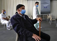 A man waits his turn to receive the Pfizer-BioNTech COVID-19 vaccine during a nationwide vaccination campaign, at the Saint George Hospital, in Beirut, Lebanon, on Feb. 16, 2021. (AP Photo/Hussein Malla)