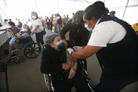 An elderly woman gets her Sinovac Biotech COVID-19 vaccine at the Americas sports center in Ecatepec, a borough on the outskirts of Mexico City, on Feb. 23, 2021. (Foto AP/Marco Ugarte)