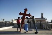 Iraqi Christians place a cross on a church in Qaraqosh, Iraq, on Feb. 22, 2021. (AP/Photo/Hadi Mizban)