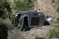A vehicle rests on its side after a rollover accident involving golfer Tiger Woods along a road in the Rancho Palos Verdes suburb of Los Angeles on Feb. 23, 2021. (AP Photo/Ringo H.W. Chiu)