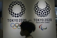 A child wearing a protective mask to help curb the spread of the coronavirus runs in front of the logos of the Tokyo 2020 Olympic and Paralympic Games on Feb. 23, 2021, in Tokyo. (AP Photo/Eugene Hoshiko)