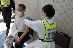 高齢者役の市職員(左)の腕に「ワクチン接種」に見立てて注射器を当てる看護師役=群馬県の渋川市民会館で2021年2月24日午後1時40分、庄司哲也撮影