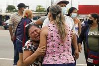 Relatives of inmates cry outside the Centro de Privacion de Libertad Zona 8 prison where riots broke out, in Guayaquil, Ecuador, on Feb. 23, 2021. (AP Photo/Angel Dejesus)