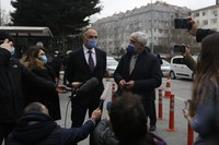 Turkish pilot Noyan Pasin, left, who was sentenced to four years and two months in prison for flying former Nissan Motor Co. chairman Carlos Ghosn out of Japan in 2019 during his dramatic escape to Beirut, Lebanon via Istanbul, talks to reporters as his lawyer looks on, following the trial outside the court in Istanbul, on Feb. 24, 2021. (AP Photo/Mehmet Guzel)