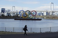 A woman wearing a protective face mask walks near the Olympic rings floating in the water in the Odaiba area in Tokyo on Feb. 18, 2021. (AP Photo/Eugene Hoshiko)