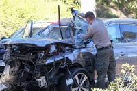 A law enforcement officer looks over a damaged vehicle following a rollover accident involving golfer Tiger Woods on Feb. 23, 2021, in the Rancho Palos Verdes suburb of Los Angeles. (AP Photo/Ringo H.W. Chiu)