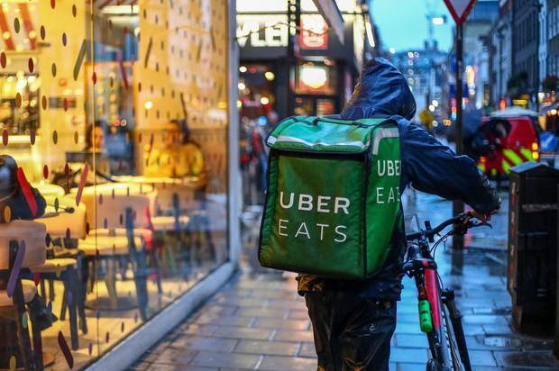 ロンドンで自転車を押すウーバーイーツの配達人 Bloomberg