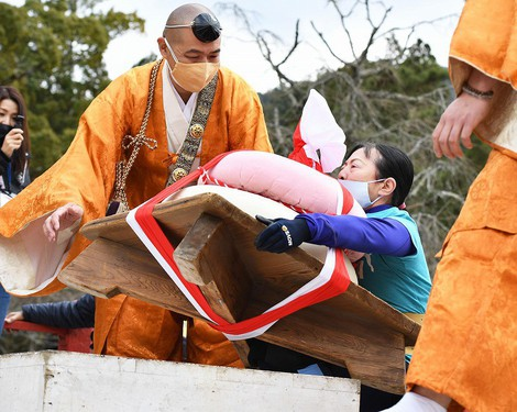 A woman lifts a huge rice cake decoration during an event at Daigo-ji Temple at Kyoto's Fushimi Ward on Feb. 23, 2021. (Mainichi/Kazuki Yamazaki)