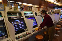 Owner Susumu Kobayashi disinfects a game machine at Kasuga Amusement Arcade in Osaka's Naniwa Ward on Jan. 20, 2021. Partitions are installed between game machines. (Mainichi/Hitoshi Sonobe)