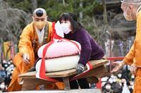 A woman lifts a huge rice cake decoration during an event at Daigo-ji Temple in Kyoto's Fushimi Ward on Feb. 23, 2021. (Mainichi/Kazuki Yamazaki)
