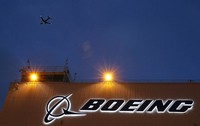In this Oct. 19, 2015 file photo, an airplane flies over a sign at the Boeing's newly expanded 737 delivery center at Boeing Field in Seattle. (AP Photo/Ted S. Warren)