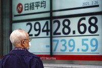 A man wearing a protective mask looks at an electronic stock board showing Japan's Nikkei 225 index at a securities firm on Feb. 26, 2021, in Tokyo. (AP Photo/Eugene Hoshiko)