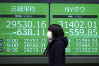An electronic stock board shows Japan's Nikkei 225 and New York Dow indexes at a securities firm on Feb. 26, 2021, in Tokyo.  (AP Photo/Eugene Hoshiko)