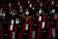 People wearing face masks to help curb the spread of the coronavirus chat as they watch a film at Poly Cinema in Beijing on Feb. 25, 2021. (AP Photo/Andy Wong)