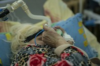 A patient with coronavirus breathes with the help of an oxygen mask at an intensive care unit in the regional hospital in Chernivtsi, Ukraine, on Feb. 24, 2021. (AP Photo/Evgeniy Maloletka)