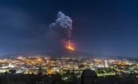 Flames and smoke billowing from a crater, as seen from the southern side of the Mt Etna volcano, tower over the city of Pedara, Sicily, on Feb. 24, 2021. (AP Photo/Salvatore Allegra)